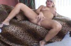 De geile huisvrouw duwt haar vingers in haar kaal geschoren kut tot een orgasme