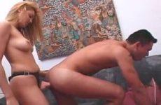 Hij likt aan haar voorbind dildo en opent zijn aars